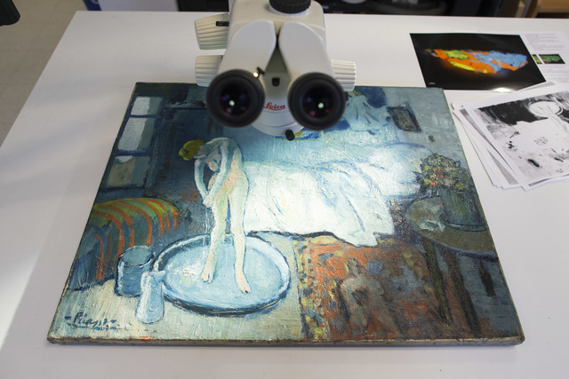 """The Blue Room,"" one of Pablo Picasso's first masterpieces sits under a microscope at The Phillips Collection, on Tuesday, June 10, 2014, in Washington. Scientists and art experts have f ..."