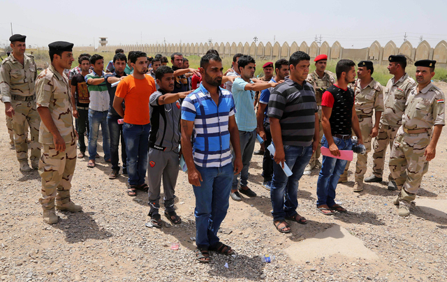 Iraqi men line up outside of the main army recruiting center to volunteer for military service on June 12, 2014, in Baghdad after authorities urged Iraqis to help battle insurgents. Iraq's militar ...
