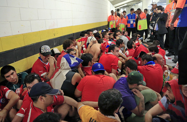 Chilean fans are surrounded by security personnel after breaking into Maracana Stadium before the group B World Cup soccer match between Spain and Chile in Rio de Janeiro, Brazil, Wednesday, June  ...