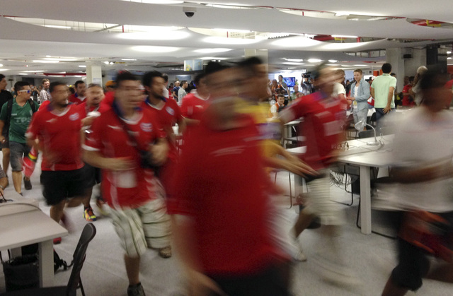 Chile fans run through the press center prior to the group B World Cup soccer match between Spain and Chile at the Maracana Stadium in Rio de Janeiro, Brazil, Wednesday, June 18, 2014.  (AP Photo/ ...