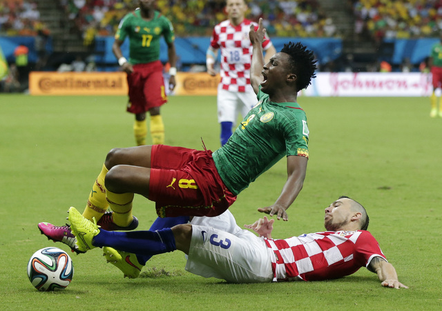 Croatia's Danijel Pranjic, right, slides underneath Cameroon's Benjamin Moukandjo during the group A World Cup soccer match between Cameroon and Croatia at the Arena da Amazonia in Manaus, Brazil, ...