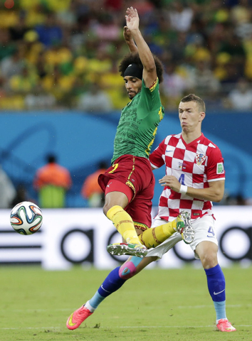 Cameroon's Benoit Assou-Ekotto, left, kicks the ball away from Croatia's Ivan Perisic during the group A World Cup soccer match between Cameroon and Croatia at the Arena da Amazonia in Manaus, Bra ...