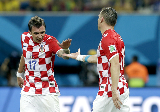 Croatia's Mario Mandzukic, left, celebrates with Croatia's Ivica Olic after scoring his side's third goal during the group A World Cup soccer match between Cameroon and Croatia at the Arena da Ama ...