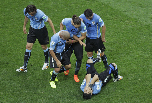 Uruguay's Luis Suarez, holding his head, is congratulated by teammates after scoring the opening goal during the group D World Cup soccer match between Uruguay and England at the Itaquerao Stadium ...