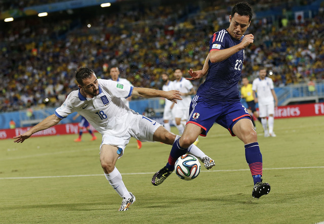 Greece's Giannis Fetfatzidis, left, challenges Japan's Maya Yoshida during the group C World Cup soccer match between Japan and Greece at the Arena das Dunas in Natal, Brazil, Thursday, June 19, 2 ...