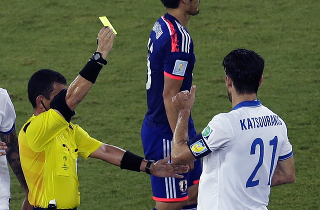 Greece's Kostas Katsouranis is booked by referee Joel Aguilar from El Salvador during the group C World Cup soccer match between Japan and Greece at the Arena das Dunas in Natal, Brazil, Thursday, ...