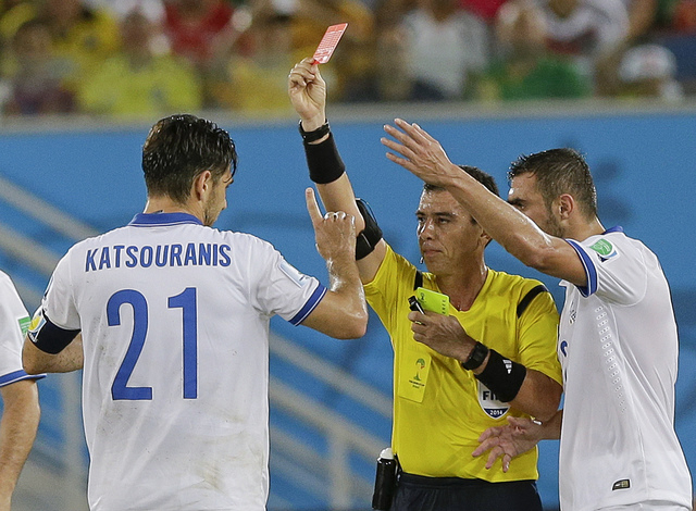 Referee Joel Aguilar from El Salvador shows a red card to Greece's Kostas Katsouranis, left, during the group C World Cup soccer match between Japan and Greece at the Arena das Dunas in Natal, Bra ...