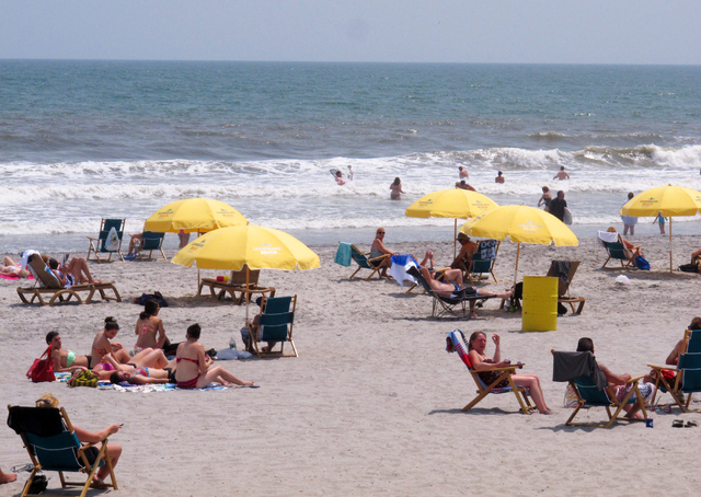In this June 27, 2013 photo, beachgoers enjoy a sunny day on the beach in Atlantic City, N.J. The city is one of five Jersey shore beach towns that don't require visitors to buy beach badges. (AP  ...