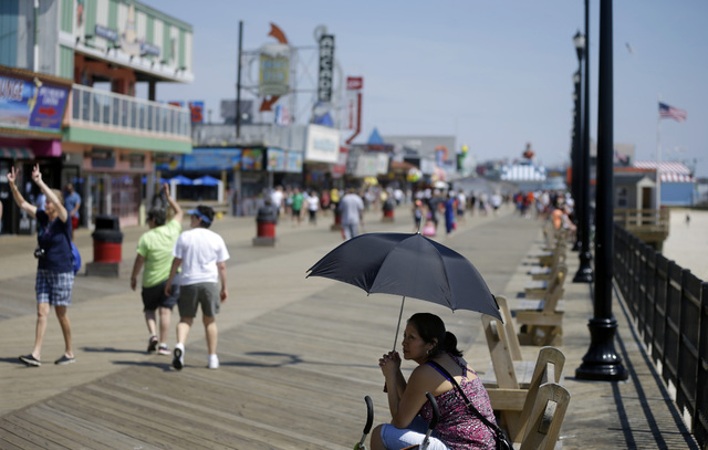 This file photo shows a woman seeking shade under an umbrella along the boardwalk on Memorial Day in Seaside Heights, N.J. Theres no better place to engage in people-watching than on the boardwalk ...