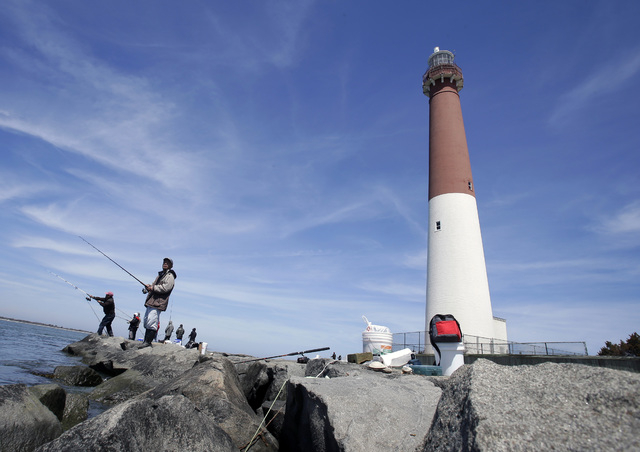 This file photo shows people fishing near the Barnegat Lighthouse on Long Beach Island, N.J. The Jersey shore is full of spots to drop a baited line or a wire trap over the side of a bulkhead, and ...