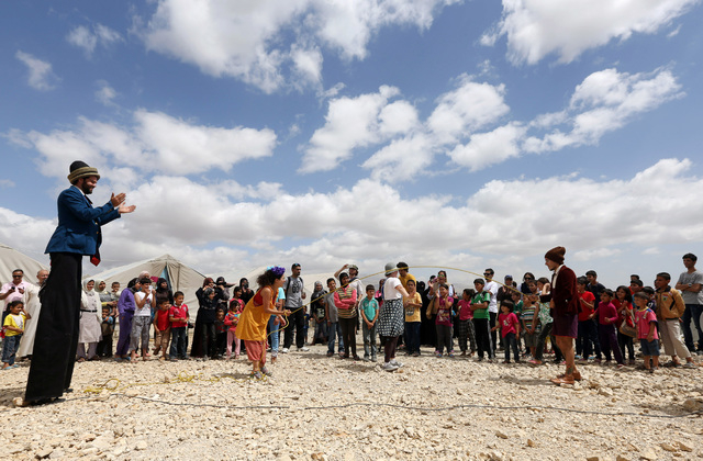 """In this June 6, 2014 photo, members of """"Clowns Without Borders"""" perform for children at a Syrian refugee camp in the eastern town of Chtoura, in Bekaa valley, Lebanon. The children are a ..."""