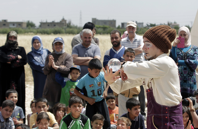 """In this June 6, 2014 photo, Chilean clown Claudio, a member of """"Clowns Without Borders"""" performs for children at a Syrian refugee camp in the eastern town of Chtoura, in Bekaa valley, Le ..."""