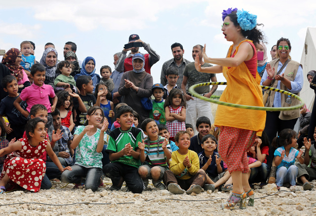 """In this June 6, 2014 photo, Lebanese clown Sabine Choucair, a ?member of """"Clowns Without Borders,"""" performs for children at a Syrian refugee camp in the eastern town of Chtoura, in Bekaa ..."""