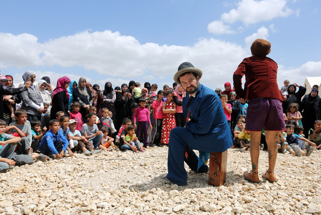 """In this June 6, 2014 photo, Chilean clown Claudio, right, and American clown David Clay, left, members of """"Clowns Without Borders,"""" perform for children at a Syrian refugee camp in the e ..."""