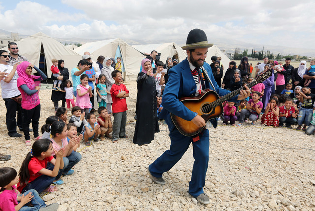"""In this June 6, 2014 photo, American clown David Clay, a member of """"Clowns Without Borders,"""" performs for children at a Syrian refugee camp in the eastern town of Chtoura, in Bekaa valle ..."""