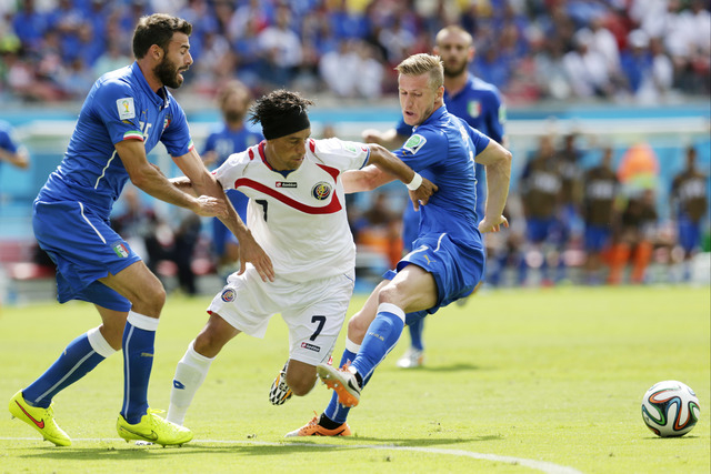Italy's Andrea Barzagli, left, and Ignazio Abate, right hold Costa Rica's Christian Bolanos as he tries to reach the ball during the group D World Cup soccer match between Italy and Costa Rica at  ...