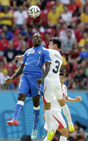 Italy's Mario Balotelli, left, and Costa Rica's Giancarlo Gonzalez head the ball during the group D World Cup soccer match between Italy and Costa Rica at the Arena Pernambuco in Recife, Brazil, F ...