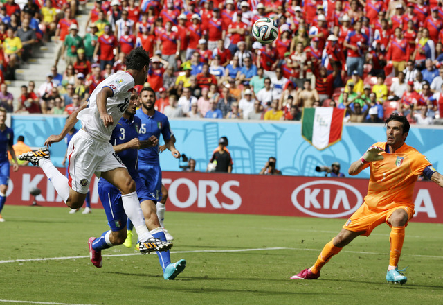 Costa Rica's Bryan Ruiz, left, heads the ball at Italy's goalkeeper Gianluigi Buffon to score his side's first goal during the group D World Cup soccer match between Italy and Costa Rica at the Ar ...