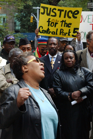 """In this Oct. 21, 2002 file photo, Dolores Wise, left, whose son Kharey Wise was one of five youths convicted in the 1989 Central Park jogger case, pumps her fist in the air as she sings """"We Shall  ..."""