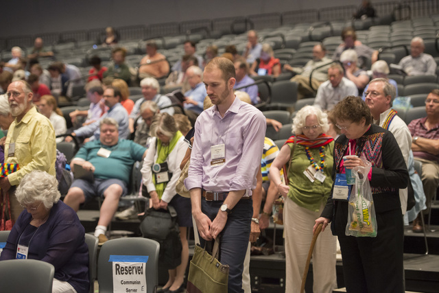 The audience takes part in an opening prayer at the 221st General Assembly of the Presbyterian Church at Cobo Hall, in Detroit, Thursday, June 19, 2014. The top legislative body of the Presbyteria ...