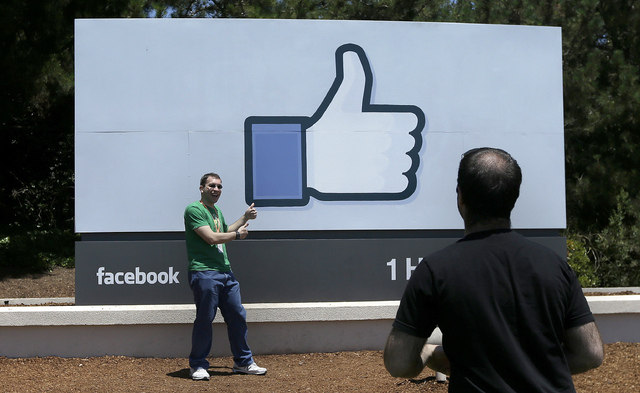 In this June 11, 2014 photo, a man poses for photographs in front of the Facebook sign on the Facebook campus in Menlo Park, Calif. In the coming weeks, Facebook will start offering advertisers an ...
