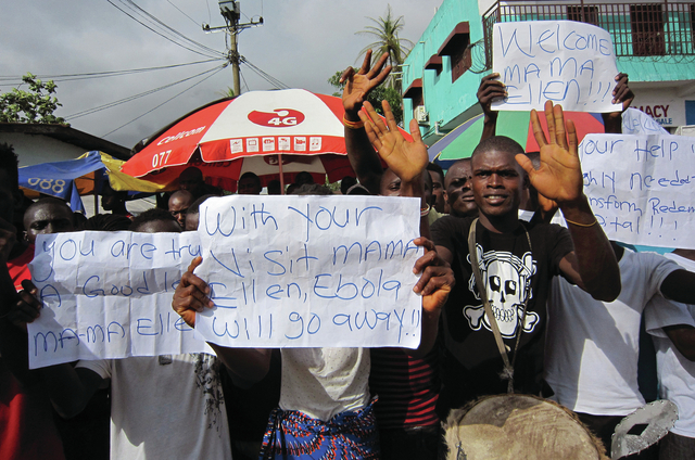 In this file photo taken on Tuesday, June 17, 2014, people protest outside a hospital as Liberia President Ellen Johnson Sirleaf  visit's the area after Ebola death's in Monrovia, Liberia. A senio ...