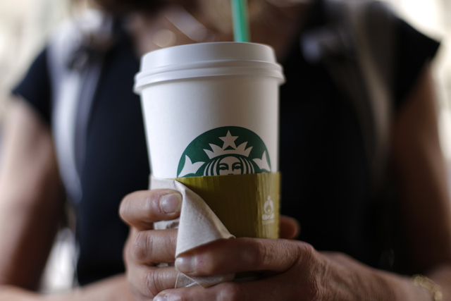 Aa woman holds a coffee drink outside a Starbucks in downtown Chicago. Starbucks is raising prices on some of its drinks by 5 cents to 20 cents starting next week, and customers can also soon expe ...