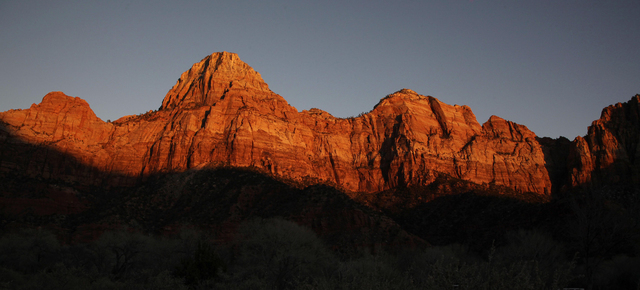 Shadows creep up on sandstone cliffs glowing red as the sun sets on Zion National Park near Springdale, Utah. The National Park Service is taking steps to ban drones from 84 million acres of publi ...