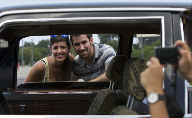 In this June 18, 2014 photo, tourists from Barcelona, Spain take a picture through the window of a Soviet-made limousine taxi cab that was once part of Fidel Castro's fleet in front of Revolution  ...