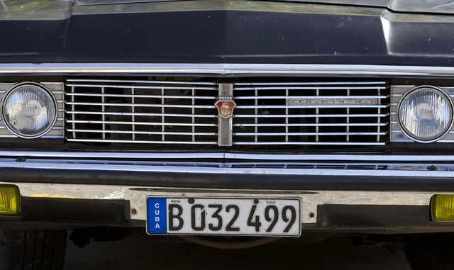"""In this June 18, 2014 photo, a Soviet-made limousine taxi cab sits parked in Havana, Cuba. In a former life they were the """"comandante's"""" cars: A fleet of black, boxy, Soviet-made limousines that f ..."""