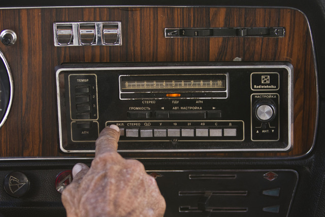 In this June 18, 2014 photo, taxi driver Moises Suarez turns on the radio inside the Soviet-made limousine taxi cab that once belonged to Fidel Castro's fleet which he rents from the government in ...