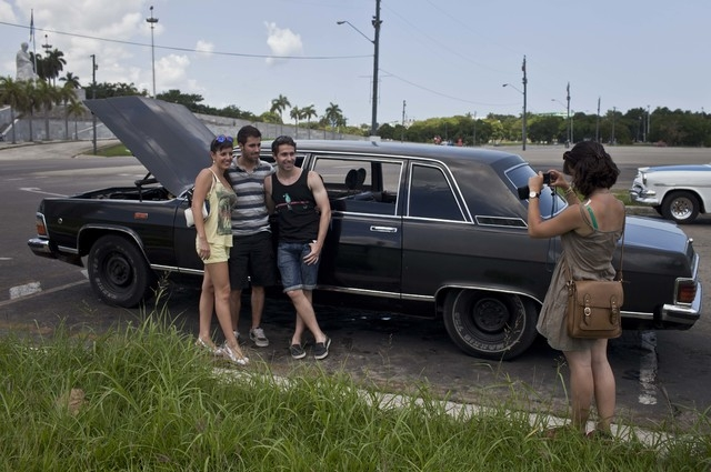 In this June 18, 2014 photo, tourists from Barcelona, Spain take a picture with a Soviet-made limousine taxi cab that once belonged to Fidel Castro's fleet in front of Revolution Plaza in Havana,  ...