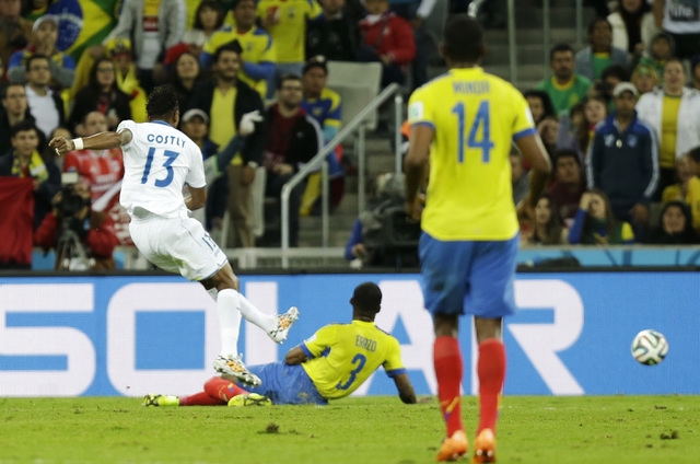 Honduras' Carlo Costly, left, kicks to score his side's first goal during the group E World Cup soccer match between Honduras and Ecuador at the Arena da Baixada in Curitiba, Brazil, Friday, June  ...