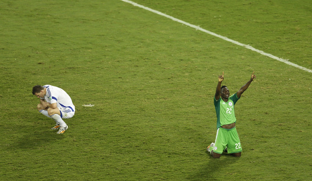 Nigeria's Kenneth Omeruo, right, celebrates as Bosnia's Edin Dzeko, left, sits on the pitch after the group F World Cup soccer match between Nigeria and Bosnia at the Arena Pantanal in Cuiaba, Bra ...