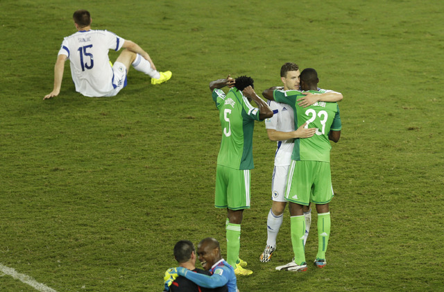 Bosnia's Edin Dzeko, second right, hugs Nigeria players after the group F World Cup soccer match between Nigeria and Bosnia at the Arena Pantanal in Cuiaba, Brazil, Saturday, June 21, 2014. Nigeri ...