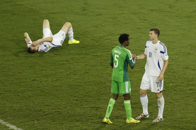 Bosnia's Edin Dzeko shakes hand with Nigeria's Efe Ambrose as Bosnia's goalkeeper Asmir Avdukic sits on the floor during the group F World Cup soccer match between Nigeria and Bosnia at the Arena  ...