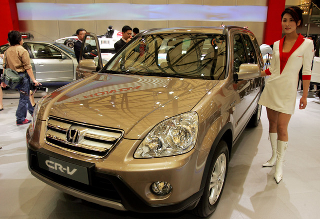 A model poses by a Honda's CR-V at Auto Shanghai 2005 exhibition in Shanghai, China in 2005. Honda, Mazda and Nissan are recalling millions of vehicles globally for defective airbags manufactured  ...