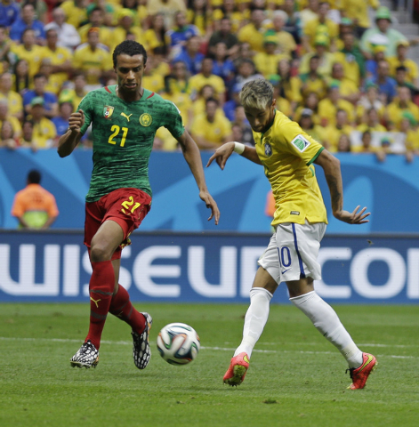 Brazil's Neymar kicks the ball past Cameroon's Joel Matip to score his side's first goal during the group A World Cup soccer match between Cameroon and Brazil at the Estadio Nacional in Brasilia,  ...