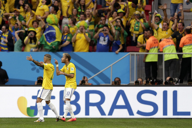 Brazil's Neymar, second left, celebrates scoring the opening goal during the group A World Cup soccer match between Cameroon and Brazil at the Estadio Nacional in Brasilia, Brazil, Monday, June 23 ...