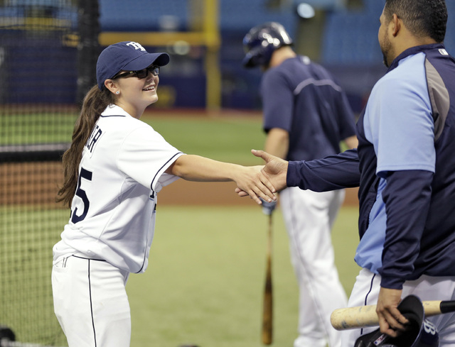 Chelsea Baker, a junior knuckleball pitcher on the Durant, Fla., High School boys baseball team, shakes hands with Tampa Bay Rays catcher Jose Molina after throwing batting practice to members of  ...