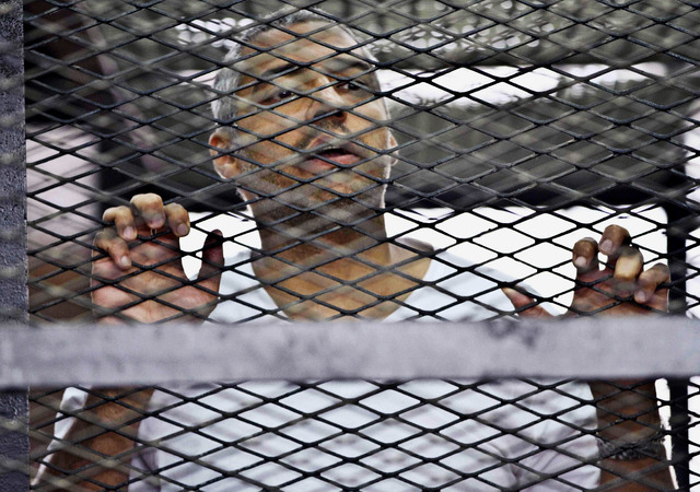 FILE - In this Thursday, May 5, 2014 file photo, Mohammed Fahmy, Canadian-Egyptian acting bureau chief of Al-Jazeera, appears in a defendant's cage at a courtroom in Cairo, Egypt. An Egyptian cour ...