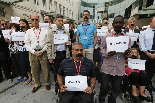 BBC journalists and staff, some with black tape over their mouths to illustrate the silencing of free speech and journalists around the world, hold a minute of silence in support of the jailed jou ...