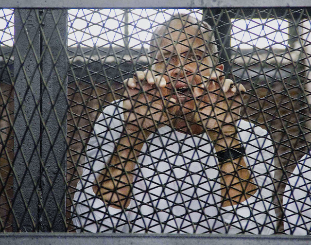 FILE - In this Saturday, May 3, 2014 file photo, Al-Jazeera's award-winning Australian correspondent Peter Greste, appears in a defendants' cage in a courthouse near Tora prison in Cairo, Egypt. A ...