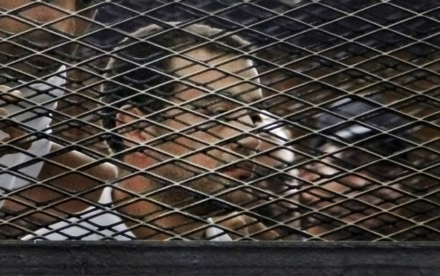 FILE - In this Monday, June 23, 2014 file photo, Al-Jazeera Egyptian producer Baher Mohamed, appears in a defendant's cage in a courtroom in Cairo, Egypt. An Egyptian court on Monday, June 23, 201 ...