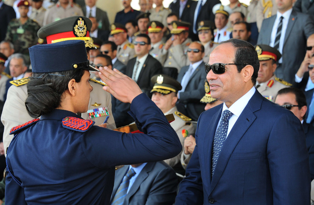This image released by Egypt's official Middle East News Agency (MENA) shows President Abdel-Fattah el-Sissi as he is saluted by a female cadet at a military graduation in Cairo, Tuesday, June 24, ...