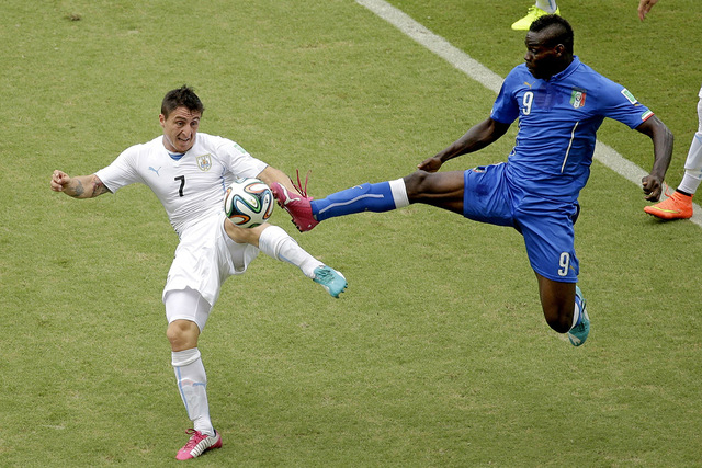 Italy's Mario Balotelli (9) and Uruguay's Cristian Rodriguez (7) battle for the ball during the group D World Cup soccer match between Italy and Uruguay at the Arena das Dunas in Natal, Brazil, Tu ...