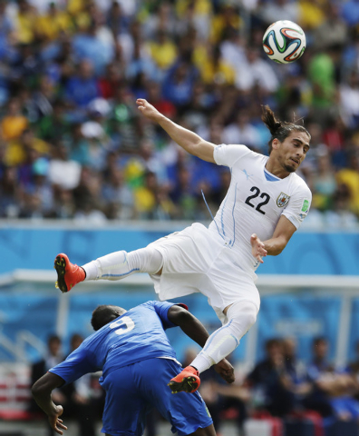 Italy's Mario Balotelli gets underneath Uruguay's Martin Caceres as he tries to head the ball during the group D World Cup soccer match between Italy and Uruguay at the Arena das Dunas in Natal, B ...