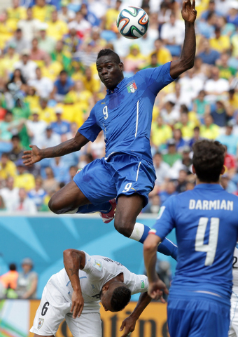 Italy's Mario Balotelli, top, collides with Uruguay's Alvaro Pereira, bottom, during the group D World Cup soccer match between Italy and Uruguay at the Arena das Dunas in Natal, Brazil, Tuesday,  ...