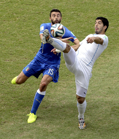 Uruguay's Luis Suarez, right, and Italy's Andrea Barzagli (15) challenge for the ball during the group D World Cup soccer match between Italy and Uruguay at the Arena das Dunas in Natal, Brazil, T ...