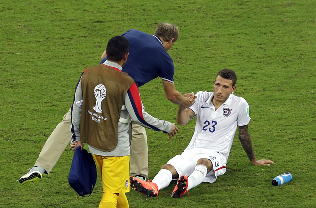 United States' Fabian Johnson, right, shakes hand with head coach Juergen Klinsmann after a 2-2 draw in the group G World Cup soccer match between the USA and Portugal at the Arena da Amazonia in  ...